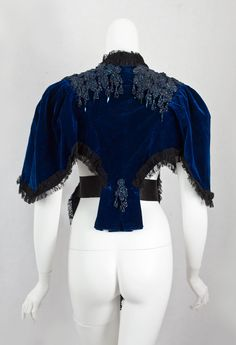 Beaded velvet mantle, c.1885. Plush royal blue velvet is the ground for the sparkling, iridescent beading. It is open and shorter in back to allow room for the centaur-shaped skirts from the final bustle period
