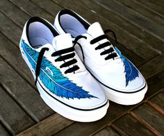 This pair of custom, hand painted White Vans Era shoes features my whimsical design of an eagle feather running up the side of each shoe. The color is different shades of blue. This order is customiza