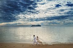 Who says you can't get a workout in on your wedding day? This couple looks like they're running toward happiness against a backdrop of stunning blue sky and rippling sea.