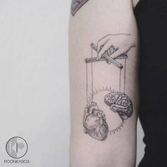Surrealist puppet tattoo on the right bicep. Tattoo artist:...
