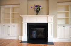 On the left is the living room with gas fireplace with a white mantel flanked by large built-in book shelves.