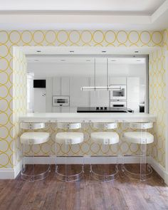 Fabulous white lacquered kitchen framed by kitchen pass through highlighted with yellow and white circles wallpaper over a white breakfast bar counter lined with vintage lucite barstools.