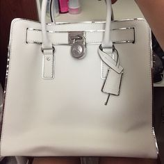 """MICHAEL KORS Hamilton Satchel Saffiano Bag Purse MICHAEL KORS Hamilton Satchel Saffiano Bag Purse Handbag White MSRP:$295 Saffiano leather Double handles with 5"""" drop; signature charm Interior features zip pocket, 2 slip pockets and key fob 12-3/4"""" W x 9"""" H x 5-1/2"""" D Includes dust bag. I only used this purse once. Michael Kors Bags Totes"""
