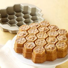 Idea; make some honey bees out of gumpaste or fondant, let dry.   Then pour thinned royal icing colored to look like honey, over the cake and add the bees before the icing hardens....Nordic Ware Honeycomb Cake Pan | Williams-Sonoma