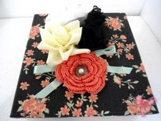 Caixa de MDF, forrada com tecido de algodão com estampa floral em fundo escuro, com aplicação de flores de voal, fita, renda e crochê na tampa. Acompanha bolsa dupla face em tecido igual ao da caixa.