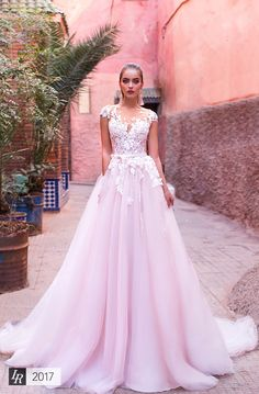 Lamia, Desert Mistress 2017, Elegance and tenderness combined in this petals embellished off-the-shoulder dress with cotton lace and delicate tulle lining. Pleated full skirt. Hem falls to floor.