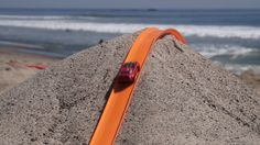 POV Footage of Cars Racing to the Finish on a Large Hot Wheels Track Built on a Beach