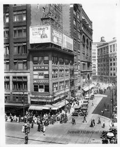 Woodward and Gratiot Avenues, taken from an elevated vantage point, and features Sallan Jewelry Store, Herbst Clothing, and The J.L. Hudson Company Department Store. Pedestrians are visible walking along the sidewalks, and crossing through the intersection. Automobiles are visible on both thoroughfares. Crowley, Millner & Co., is visible in the background.