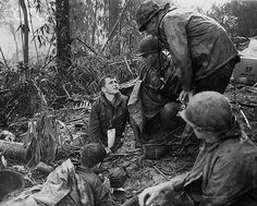 """20 May 1969, A Shau Valley, South Vietnam --- May 20, 1969 - A Shau Valley, South Vietnam: A wounded 101st Airborne trooper (with white tag) talks with a chaplain on """"Hamburger Hill"""" overlooking the A Shau Valley other wounded soldiers sit with him in the rain as they await evacuation. --- Image by © Bettmann/CORBIS"""