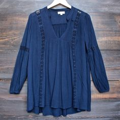 Gauzy navy blouse featuring a flowy babydoll silhouette with sheer lace trim.