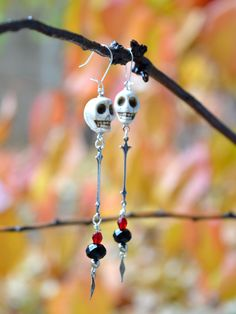 Rocker style long silver earrings with white howlite skulls, red chalcedony beads, and black glass beads. Silver-tone findings. Thin, french hook ear wire. These earrings are 5 inches long. Long silve