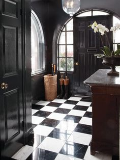 dramatic foyer in black and white check and those arched windows - squares in window panes reflected in tiles -