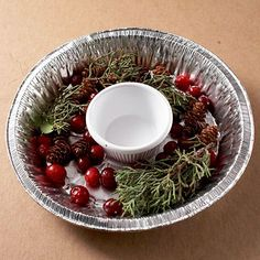 If you use a regular round baking pan, start by placing a small dish in the center to make the wreath. Arrange berries, holly, birdseed, greenery, and pinecones inside the pan as desired. Fill with water and freeze (in your freezer or outdoors). Once frozen, dip the bottom of the pan in warm water to loosen the ice wreath. Loop raffia around the wreath and hang from a tree branch.