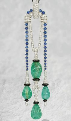 This is different:  A FINE ART DECO GEM-SET PENDANT, BY CARTIER   The central pendant designed as two fluted emerald beads with pavé-set diamond surmount and onyx rondelle detail flanked by similar pendants suspended from a graduated line of cabochon sapphires to the pavé-set diamond suspension loop, circa 1925, 12.0 cm long  Signed Cartier, No. 2317527