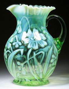Daffodil water pitcher in green opalescent glass with circular crimped rim and applied transparent green handle by H. Northwood Co, USA