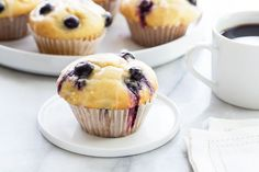 Blueberry Doughnut Muffins are topped with a sweet and tangy lemon glaze.  Perfect with a cup of afternoon tea or your morning coffee!