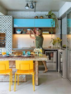 Um projeto de cozinha encantador que une elementos rústicos, modernos e cores em um único ambiente aberto e integrado.