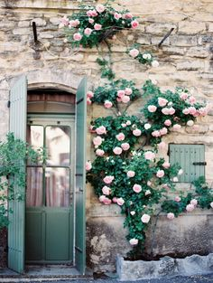Green door on a stone house with roses