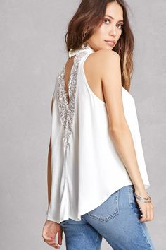 A textured woven top featuring a mock neck with a button back closure, a front V-cutout, lace back detail, sleeveless cut ,and swing silhouette.<p>- This is an independent brand and not a Forever 21 branded item.</p>