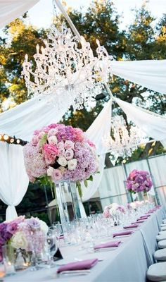 Outdoor drapped wedding reception with purple floral and crystal chandelier