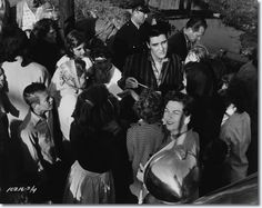 Elvis on location at Lake Pontchartrain Shack, New Orleans March 4,1958. Elvis signs some autographs for waiting fans. Elvis is wearing a shirt not seen in the movie, so he is either arriving or departing the location. -