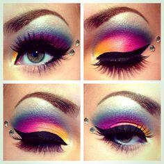 Stunning orange, pink, and blue eyeshadow! The bold black eyeliner, rhinestones, and false lashes glam up the look.