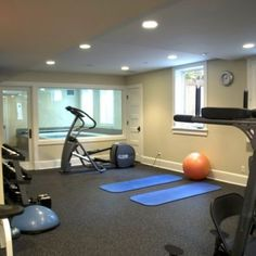Home gym behind half wall of glass with glass door. Other half of basement is kids play room so they play while you workout.