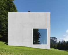 Haus Rüscher by OLKRÜF, Austria - Large windows pierce the concrete facade on different sides to give residents clear views across the mountain and forest landscape.