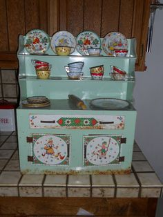 Vintage tin toy kitchen cabinet with the metal dishes