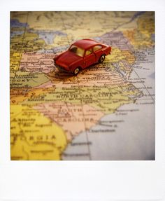 It might be fun for the boy to track our progress with one of his cars on a map, since he loves (a) cars and (b) maps so much.  It would also make a nice new section of a hypothetical road trip album to take a picture of the same car on a new place of the map for each state.