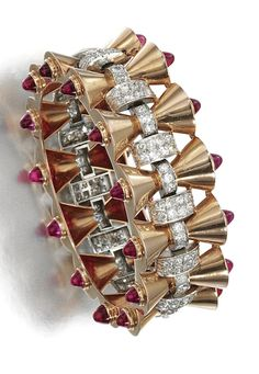 SYNTHETIC RUBY AND DIAMOND BANGLE, 1940S The hinged bangle designed as a series of polished conical links set to each terminal with cabochon synthetic rubies, accented with circular- and single-cut diamonds, inner circumference approximately 155mm.
