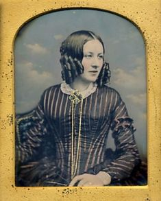 ca 1850's hand-tinted daguerreotype portrait of a young woman posed in front of a cloud backdrop. Amazing striped silk dress and fringe sleeve caps. Beautiful gold jewelry and cute side ringlet curls.