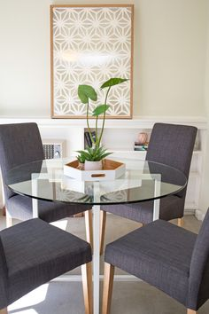 Small dining area, small apartment, round glass top dining table, grey upholstered dining chairs, plant vignette