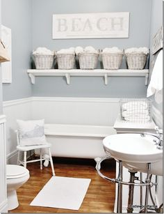 This blue-grey an white bathroom is serene and practical - simple baskets on a simple shelf amplify the storage.