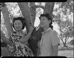 Florence Yamaguchi (left), and Kinu Hirashima, both from Los Angeles, are pictured as they stand under an apple tree at Manzanar internment camp. (Their hairdos are amazing - especially Hirashima's bangs!)
