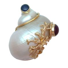 "SEAMAN SCHEPPS The large white turbo shell wrapped with 14kt gold wire and set at the terminals with a cabochon ruby and sapphire, further accented with a swag of yellow gold ""seaweed"", signed P.S.V. of Seaman Schepps (for Patricia Schepps Vaill, his daughter, who was active beginning in the late 1960s), with sturdy double pin clip back and safety catch, ca. 1960s."