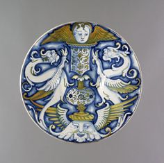 Plate with sloping sides and slightly convex centre, slight foot ring. Earthenware covered front and back with presumed tin glaze. Painted on front in blue, with a brownish lustre with green and yellow tints. In centre, on a winged mask, a tall vase or pedestal with a winged cherub head on top; on either side a winged monster.