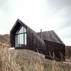 RAW Architecture Workshop have designed this angular black house at Camusdarach Sands with huge windows for taking in the views over the Scottish landscape. The shapes of these expansive gable windows are a play on… Architecture Résidentielle, Amazing Architecture, Workshop Architecture, Sand House, Highland Homes, Timber House, Grand Designs, Black House, House Design