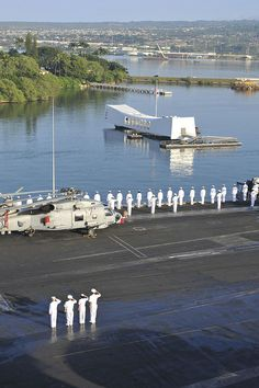 PEARL HARBOR (Dec. 3, 2013) Sailors render honors as the aircraft carrier USS Nimitz (CVN 68) passes the battleship USS Arizona (BB 39) memorial upon their arrival to Pearl Harbor. Nimitz is in Pearl Harbor for a scheduled port visit during their transit home after an eight-month deployment to the U.S. 5th, 6th, and 7th Fleet areas of responsibility. (U.S. Navy photo by Mass Communication Specialist 3rd Class Eric M. Butler/Released)