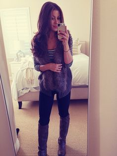 Black leggings with black striped top paired with brown fur vest and brwn boots.