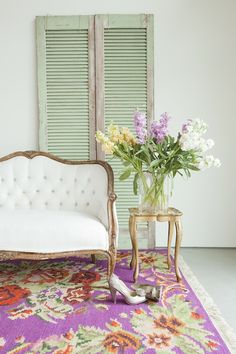 white settee on lavender floral rug