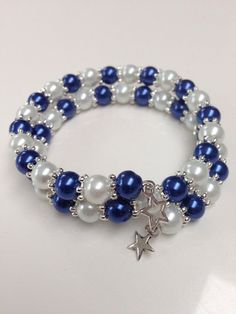 This is a stunning handmade two strand memory wire bracelet featuring gorgeous glass pearl beads, separated by silver plated snowflake spacers and finished with a pretty Tibetan silver dangling star charm.  Order to comprise of five bracelets: one child size, three small adult sizes and one larger adult size.
