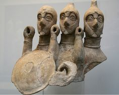 """Three-bodied Cypriot warrior figure c.580 BC From Pyrga, Cyprus. This terracotta figure from a sanctuary deposit is believed to represent a supernatural warrior with three bodies and heads, rather than a close formation of three figures. The heads are protected by conical helmets with cheek pieces and massive neck protectors. Each embodiment once held a round shield and a spear, giving an idea of how hoplites """" locked shields """" during the final stages of the advance to contact."""