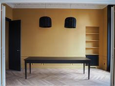 Contemporary dining room for a flat in Paris. Yellow wall colour, Indian Yellow from Farrow and Ball. Black painted woodwork, basket lighting from Paola Navone. Original wooden french parquet sanded back to natural colour and sealed only for protection