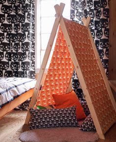 A bedroom with curtains and cushions with black cat face pattern and a tent made of wooden posts and a fabric with orange cat face pattern.