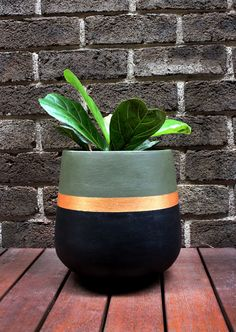 Hand-painted lightweight plant pot in khaki and black with a metallic gold stripe. This is a striking design which will add a touch a glamour to your home! The material of the pot is fibreglass and painted using water-based paint. Small - 25 x 25cm Medium - 35 x 35cm Large - 45 x 45cm  Our pots have their own personality and imperfections which is what makes them unique. As the pots are hand painted they are delicate and need to be handled with extra care. They are intended for indoor use or ...