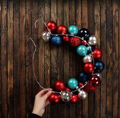 Die Frau fädelt Weihnachtsbaumkugeln auf den Kleiderbügel. Das Ergebnis ist absolut großartig!
