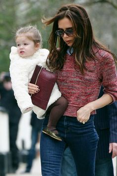 Perfecta en brazos de mamá con abrigo furry de Chloé y bailarinas color cobrizo.