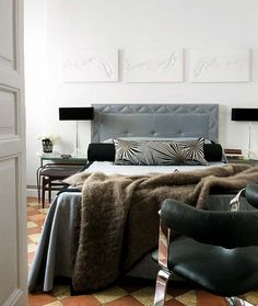 raul martins bedroom--upholstered grey velvet headboard with nailhead trim, bolster pillow, faux fur throw