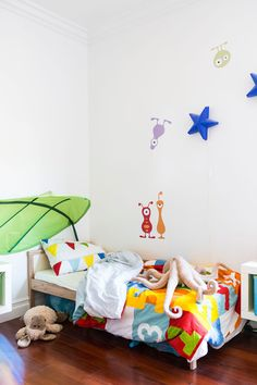 An Imaginative L.A. House Brimming with Creativity: Bright bedding and wall decals bring punches of color to a kids playful bedroom.